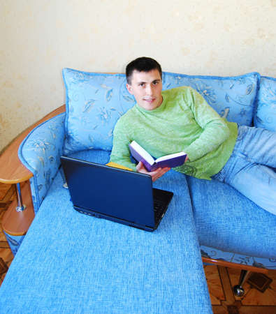 Attractive young man reading a book in bed. photo