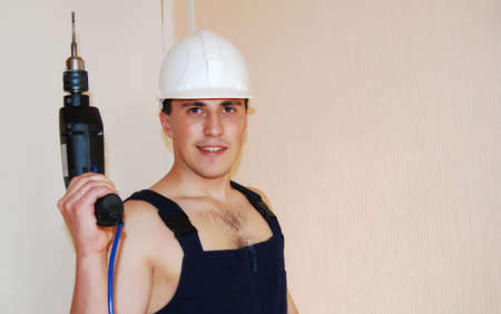 Muscular young man in a builder uniform. Stock Photo - 8038060