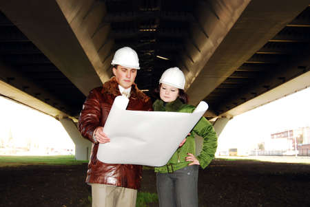 Young architects looking at blueprint. Stock Photo - 8040849