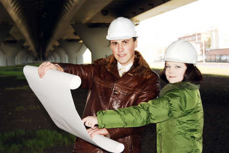 Young architects looking at blueprint. Stock Photo - 8040861