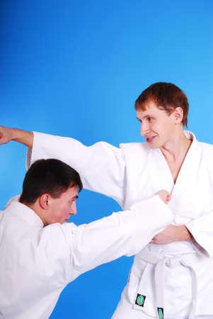 Two karatekas on a dark blue background. photo