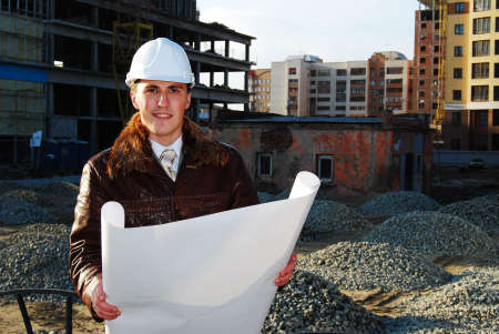 builder with blueprints on construction site . photo
