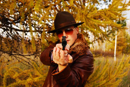 Dangerous looking mafia type with revolver.  photo