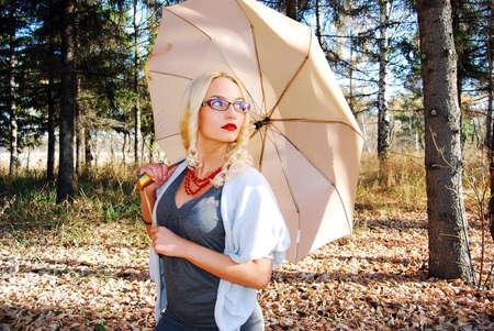 Girl under umbrella in autumn forest.