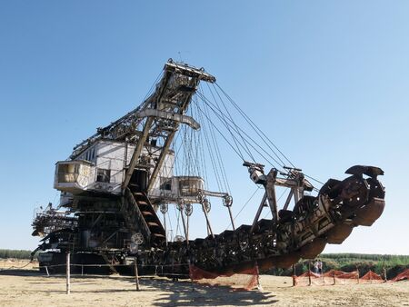 Giant old absetzer rusts in a sand quarry. Huge mining excavator.