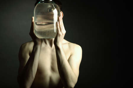 Young naked man with glass vase photo