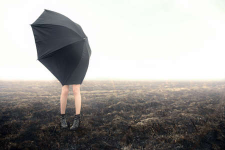 girl with umbrella on black field photo