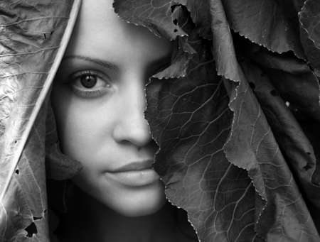 portrait of young beautiful girl with big leaves on head photo