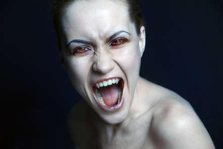 scared woman: sexy vampire. Studio photo.