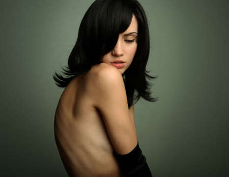 Elegant nude girl with magnificent black hair. Studio portrait. photo