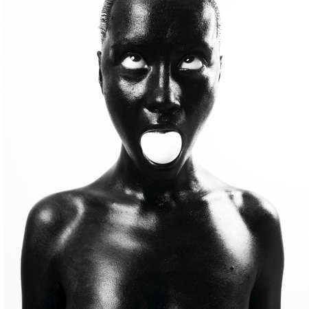 Fashion portrait of made up black woman with egg photo