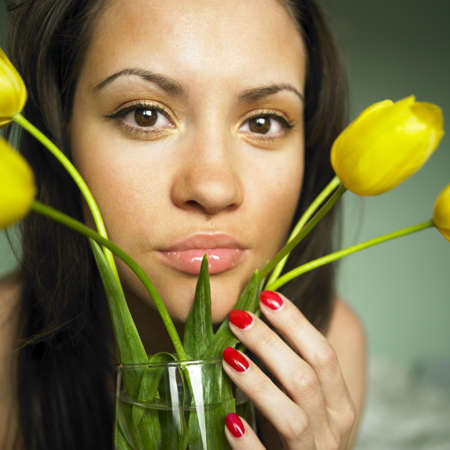 Fashion portrait of young charming woman with bouquet of tulips photo