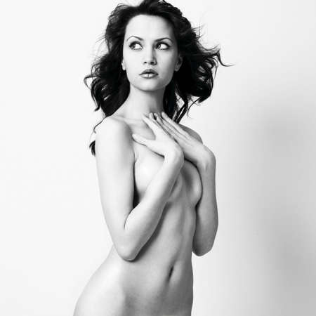 20s nude: Elegant nude woman with curly hair. Studio portrait.