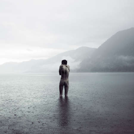 Picturesque landscape. Young man in lake Stock fotó
