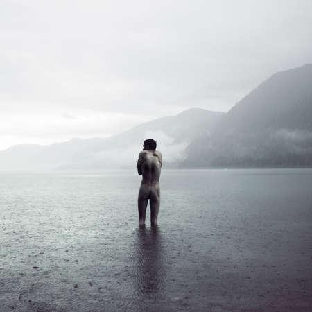 Pittoresco paesaggio. Giovane uomo nudo nel lago Archivio Fotografico