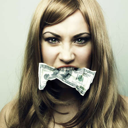 Studio portrait of the young woman eating 100 US dollars photo