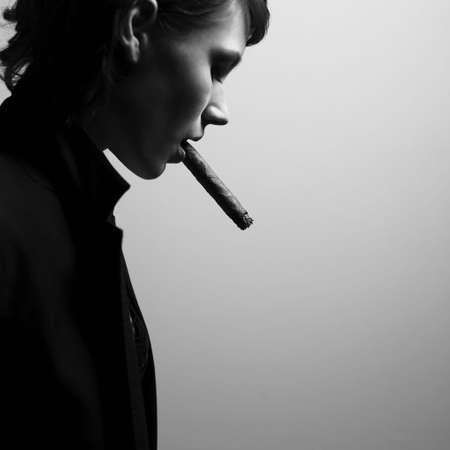 Woman smoking cigars. Studio fashion photo