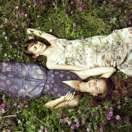 Two romantic girl lying on flower meadow photo