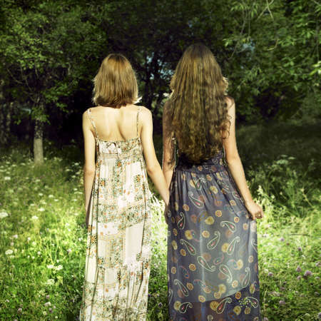 Figures of two romantic girls in green wood photo