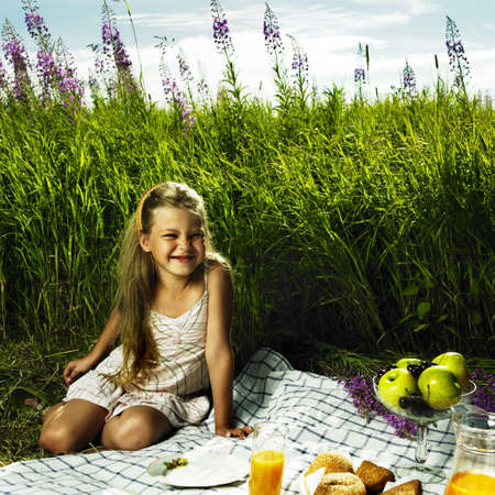 little girl sitting: Photo of charming little girl at picnic Stock Photo