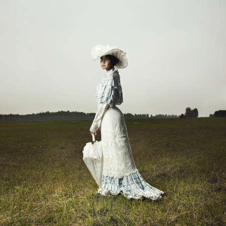historic: Slender woman in vintage dress for promenade