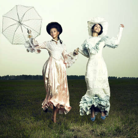 Two beautiful woman in vintage dress on nature photo