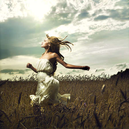 Portrait of romantic woman running across field photo