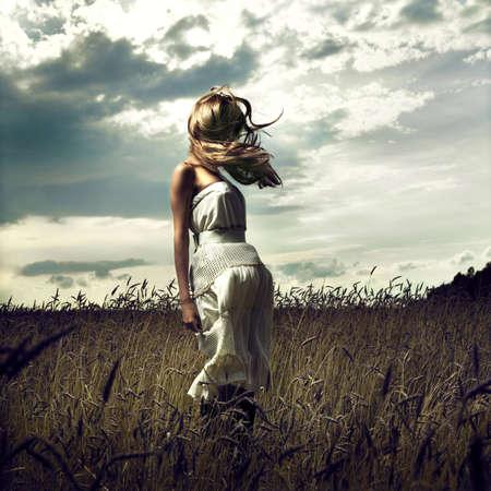 vent: Portrait de sauter des femmes dans le champ de bl�  Banque d'images