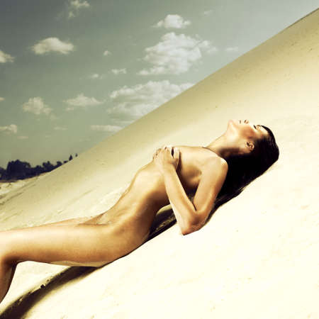 Elegant nude woman laying on the sand Stock Photo - 7706032