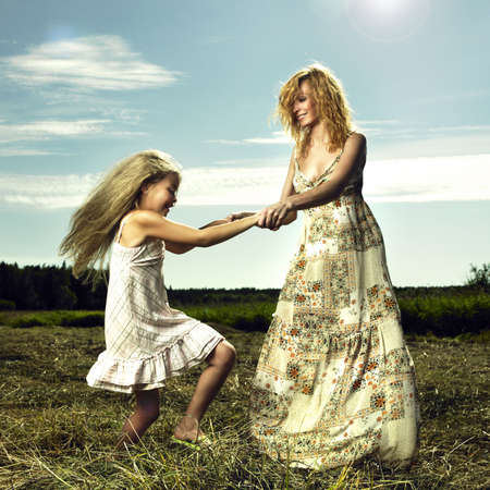 hay field: Mother and daughter having fun on field