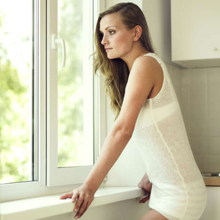 Portrait of beautiful pensive girl at window photo
