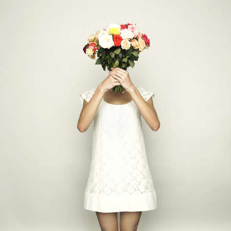 Girl with a head-bouquet of roses. Surreal portrait photo