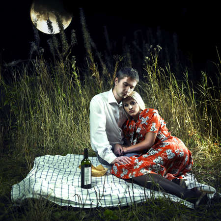 Beautiful young lovers in the moonlight picnic photo