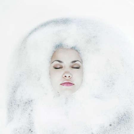Young beautiful girl relaxing in the bath with foam photo
