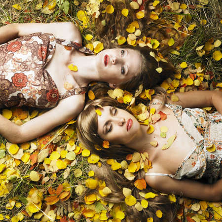 Two romantic girl lying in autumn leaves photo