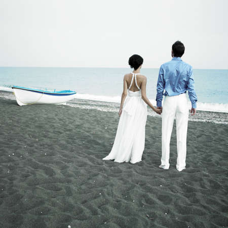 Romantic bride and groom are looking at the sea photo