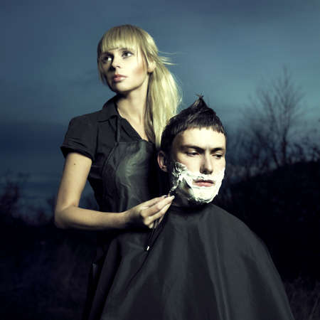 Beautiful woman barber shaves a courageous man. Surreal picture photo