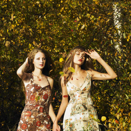 Two romantic girl surrounded by autumn leaves Stock Photo