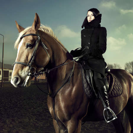 Elegant woman in a black coat riding on a brown horse Stock Photo