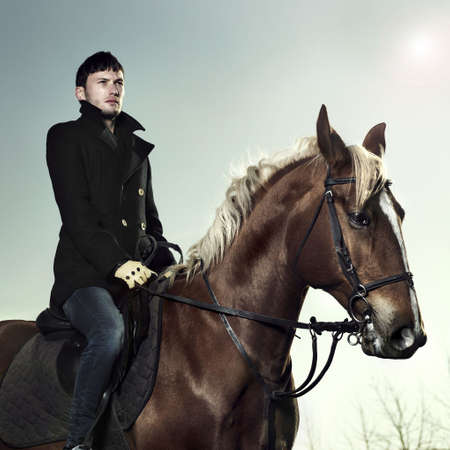 Handsome man in a black coat riding on a brown horse Stock Photo - 8105846