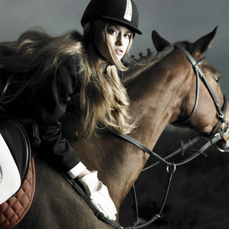 Elegant woman in a black coat riding on a brown horse photo