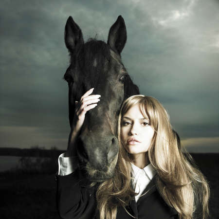Fashionable portrait of a beautiful young woman and horse photo