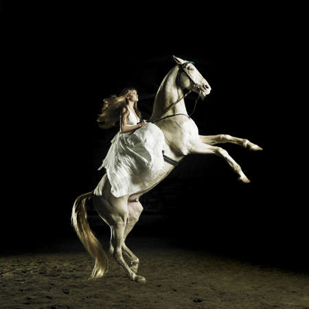 Beautiful blonde in a white dress on a white horse