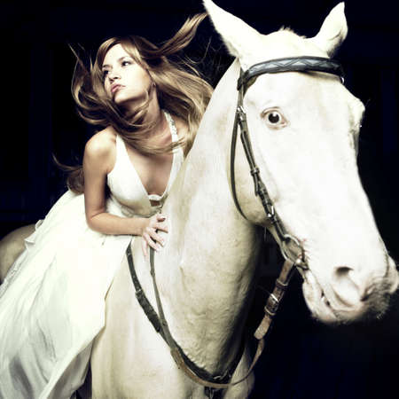 Beautiful blonde in a white dress on a white horse photo