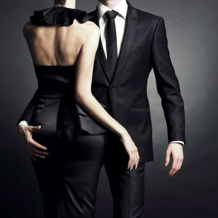 Conceptual portrait of a young couple in elegant evening dresses photo