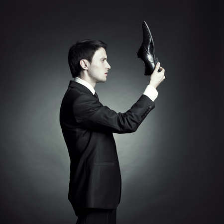 Surreal portrait of a stylish man in an elegant suit and shoes in hand photo