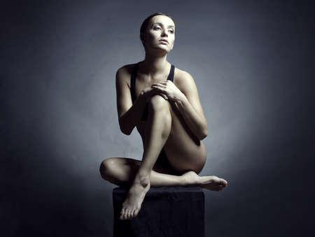 donna completamente nuda: Donna nuda seduta bella su sfondo nero