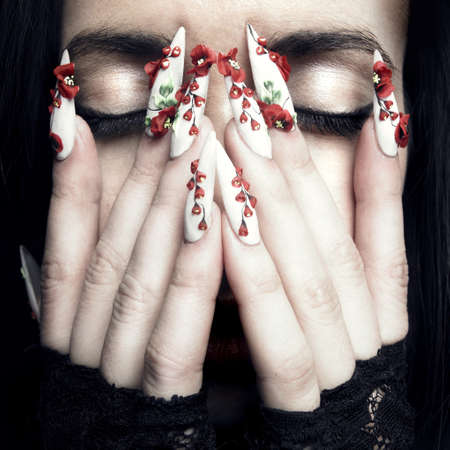 Portrait of a beautiful young woman with long designer nails photo