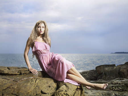 wet clothes: Fotos de la bella mujer en ropa mojada en una costa rocosa
