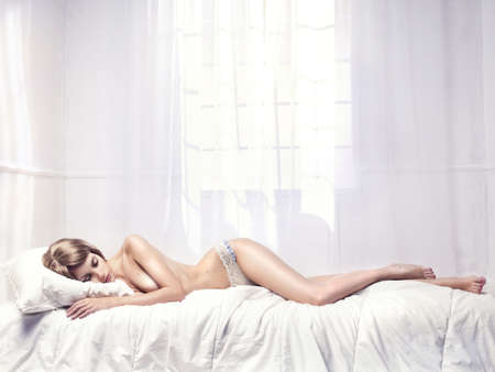 nude: Fashionable photo sleeping nude woman in a white room